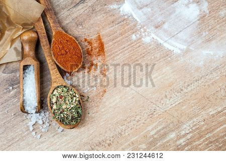 Flat lay of wooden spoons with spices,  coarse salt and paprika for cooking scatered on a table