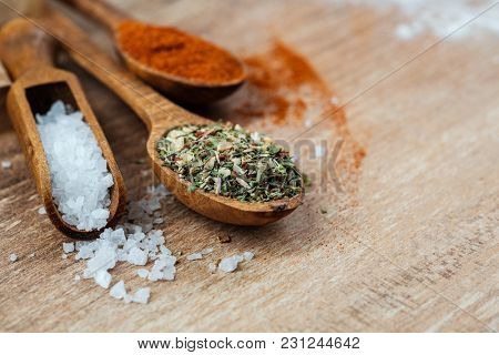 Wooden spoons with scattered coarse salt, spices and cinnamon for cooking on a table