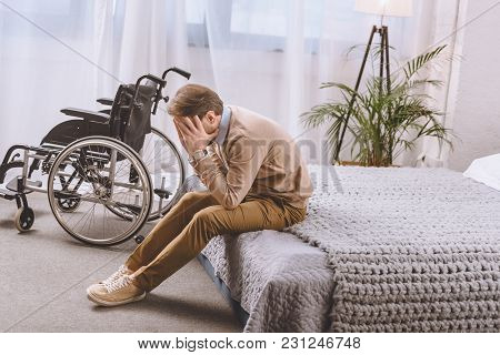 Upset Man With Disability Sitting On Bed And Covering Face With Hands