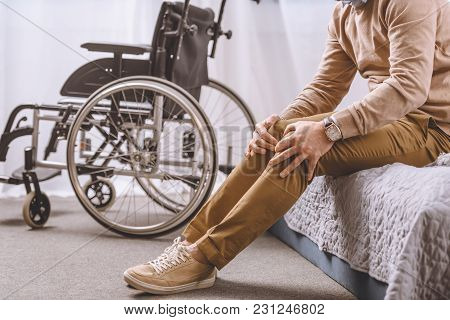 Cropped Image Of Man With Disability Sitting On Bed And Touching Legs