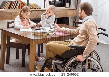 Father On Wheelchair Helping Daughter And Son With Education At Home