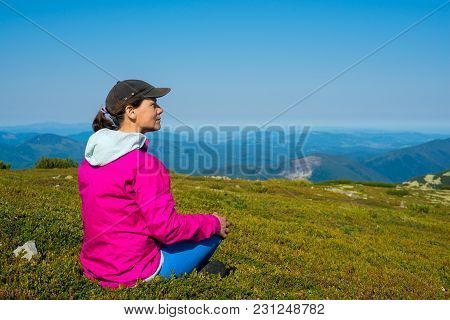 Happy Proud Woman, Hiker Sits On A Green Mountain Meadow On A Sunny Day, Admires The Amazing View Of
