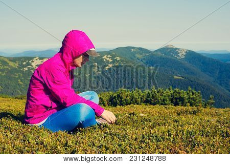 Sporty Woman, Hiker Sits On A Green Mountain Meadow On A Sunny Day, Dreams And Meditates Alone With