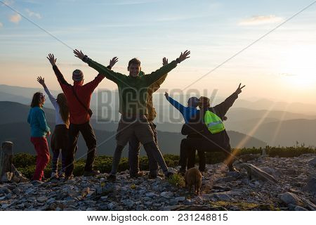 Happy Hikers, Friends With Open Arms Are Standing On A Top, Admiring The Panorama Of Mountains In Th