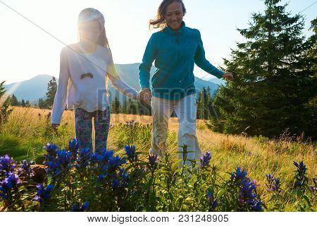 Laughing Mom And Her Teenage Daughter Are Running Around In A Alpine Meadow Among Lush Green Grass A