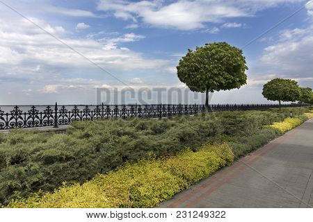 A Paved Stepped Road In A Beautiful Park Passes Along The Embankment Of The River With Ornamental Fl
