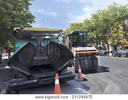 Among The Summer Noon, A Heavy Asphalt Paver And Road Vibrating Roller Compactor Is Ready To Repair