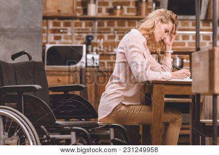 Side View Of Disabled Woman In Wheelchair Taking Notes While Working At Home