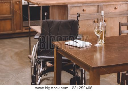 Wheelchair Standing Near Table With Wine Bottle, Glasses, Notebook And Pen