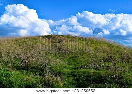 Lush Green Field On Rural Grasslands With Cumulus Clouds Beyond During Atmospheric Instability