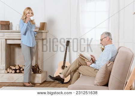 Mature Man Reading Book While Woman Drinks Tea In Light Room