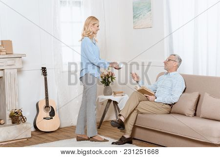 Mature Man Reading Book While Woman Serves Him Tea In Cozy Room