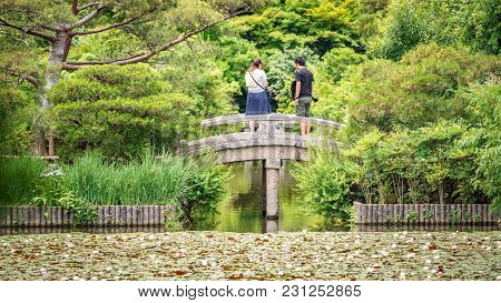 Long Rear View Of Couple Over Stone Bridge In The Park