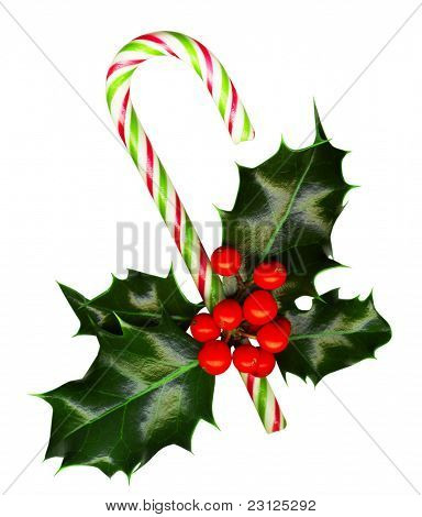 Clipping path. Candy cane with pretty holly leaves and berries on white background