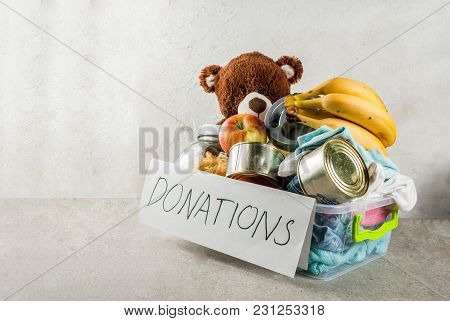 Plastic Donation Box With Toys, Clothes And Food, White Grey Background Copy Space