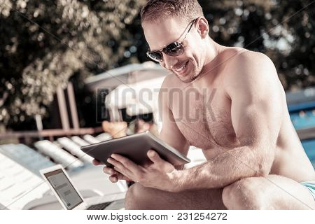 Positive Vibes. Joyful Young Man Wearing Sunglasses Sitting On A Sunbed And Smiling While Looking At