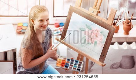 Artist painting on easel and palette in studio. Authentic happy girl child paints drawing of spring flowers in morning sunlight dawn light toning window background. Children's painting competition.