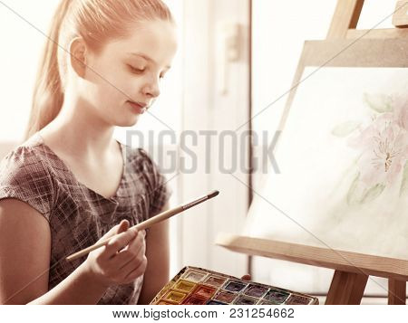 Artist painting on easel and palette in studio. Authentic girl paints with brush in morning sunlight dawn light toning . Drawing spring flowers. Discounts on goods for artists. Stylize photo movie.