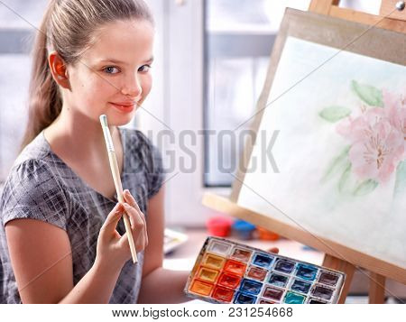Artist painting on easel and palette in studio. Authentic girl paints with oil brush in morning sunlight. Drawing of spring flowers. Girl dreams of enrolling in art school. Portrait of young artist.