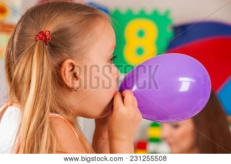 Break school in painting class. Small student painting in art school class. Physical education of little girl is blowing a purple balloon. Craft drawing develops creative abilities of children.