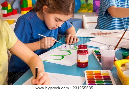 Small students painting in art school class. Child drawing by paints on table. Boy and girls in kindergarten. Drawing education develops creative abilities of children. Art children's school.