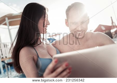 Check This Out. Millennial Couple Sitting Next To Each Other And Smiling Cheerfully While Using A To