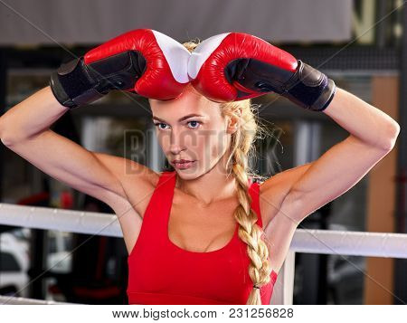 Sport boxing woman wearing red gloves. Girl is in corner of ring and is preparing for martial arts battle.