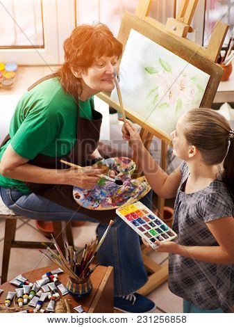 Artist painting easel in studio. Authentic grandmother and kids girl paints with palette watercolor paints palette and brush morning sunlight. Grandmother teaches grandsons of artist's profession.