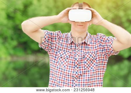 Man In Helmet Of Virtual Reality Against The Background Of Nature.