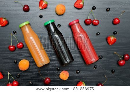 Three Bottles Of Juice And Fruits. Black Wooden Background. Food Concept