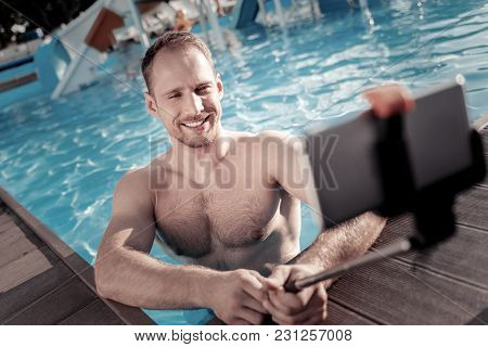 One More Shot. Selective Focus On A Radiant Young Man Grinning Broadly While Standing In A Swimming