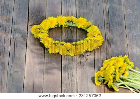 Wreath Of Dandelions On A Wooden Table. Summer