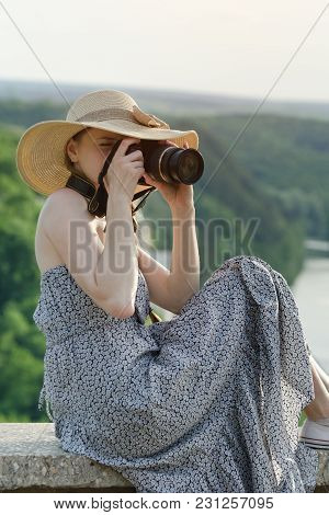 Girl In A Sundress And A Hat With A Camera. Green Forest And River In The Distance
