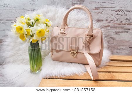 Pink Hahdbag And Bouquet Of Daffodils On White Fur. Fashionable Concept