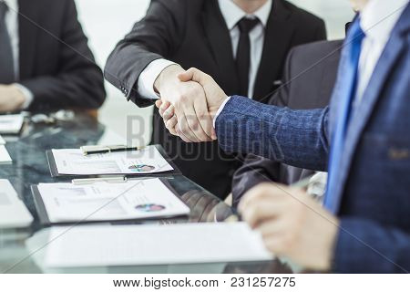 Handshake Of Two Lawyers After Discussing The Terms Of A Financial Contract At A Desk In The Office
