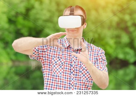 Man In Helmet Of Virtual Reality Against The Background Of Nature. Show Ball