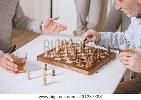 Cropped Image Of Men Playing Chess While Sitting At Table