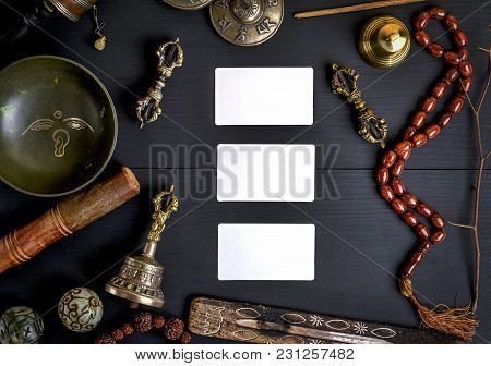 Three Empty White Business Cards In The Midst Of Asian Religious Objects For Meditation And Alternat