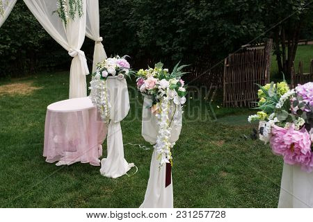 Details Of Beautiful Wedding Ceremony In The Park. Racks With Flowers Near The Arch. Décor