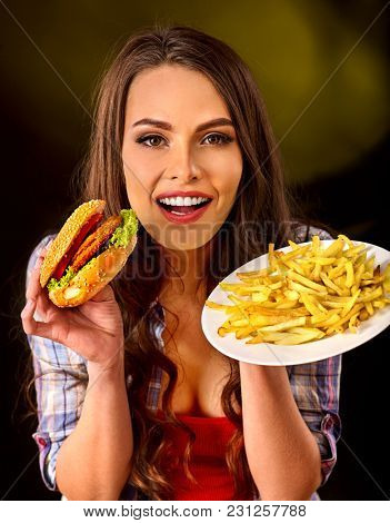 Woman eating french fries and hamburger. Portrait of student consume fast food on table. Girl trying to eat junk. Advertise fast food on daek background. Expensive fast food restaurant.