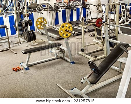 Fitness Room with jogging treadmill and Weight Machines. Group of treadmill in row big sport gym. Empty gym with sportsmen and sportswomen pictures on walls. Best fitness club.