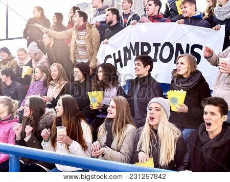 Fans cheering in stadium holding champion banner and singing on tribunes. People are waiting for start of sports competitions. People holding banner with Champion banner happily eating popcorn.