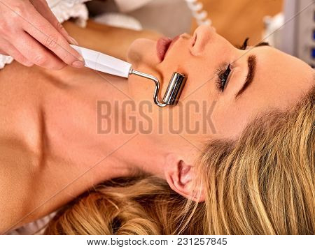 Facial massage at beauty salon. Electric stimulation skin care of woman. Professional microcurrent lift face. Anti aging neck non surgical treatment. Improvement of skin condition.