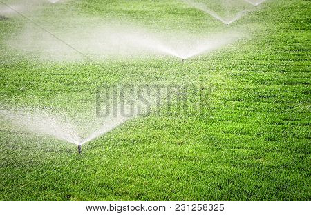 Several Garden Sprinklers On The Grass Field