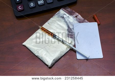 Drugs Powder And A Syringe On Desk Office.  Drug Addiction. International Day Against Drug Abuse