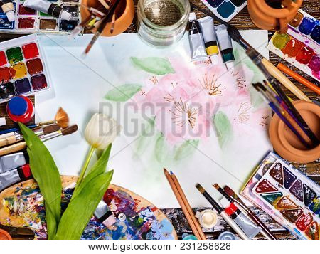 Authentic paint brushes still life in art class school. Group of brush in clay jar. Bouquet of flowers as symbol of spring discounts. White tulip in the foreground. Spring discounts on drawing course.