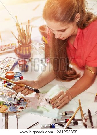 Authentic artist children girl paints with set palette watercolor paints palette and brush in morning sunlight. Sun flare private business in drawing for student. Indoor home interior handmade crafts.