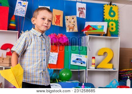 Dreams flight of child in kindergarten. Happy boy child playing with origami airplane in kindergartener or school.