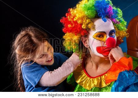 Single parent family. Tired Halloween mom after work as clown on birthday on dark background. Adult child relationship. Social problem mad parent. Person hates his profession and unhappy with himself.