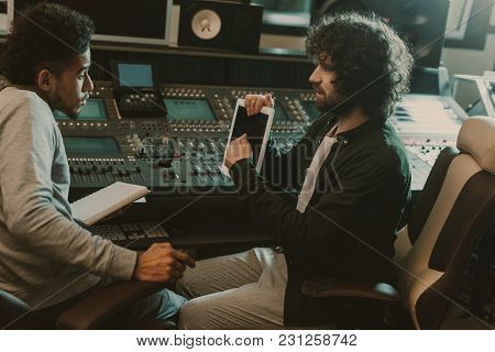 Man Showing Blank Tablet Screen To Sound Producer At Recording Studio